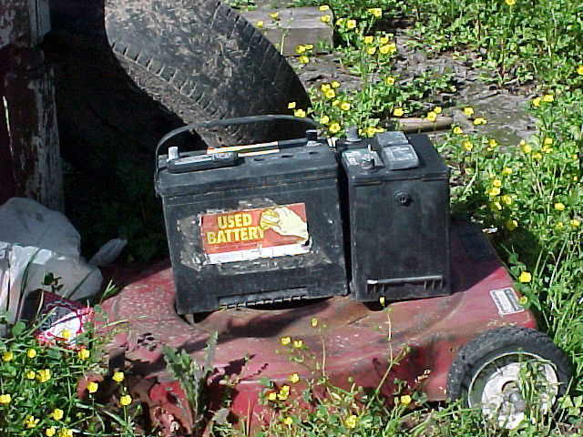 Image of a trashed lawn mower and used battery just left laying around.