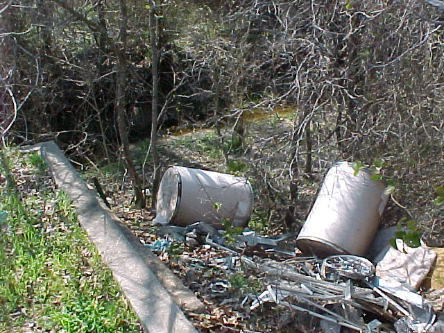 Barrels and other metal components piled illegally on the side of the road