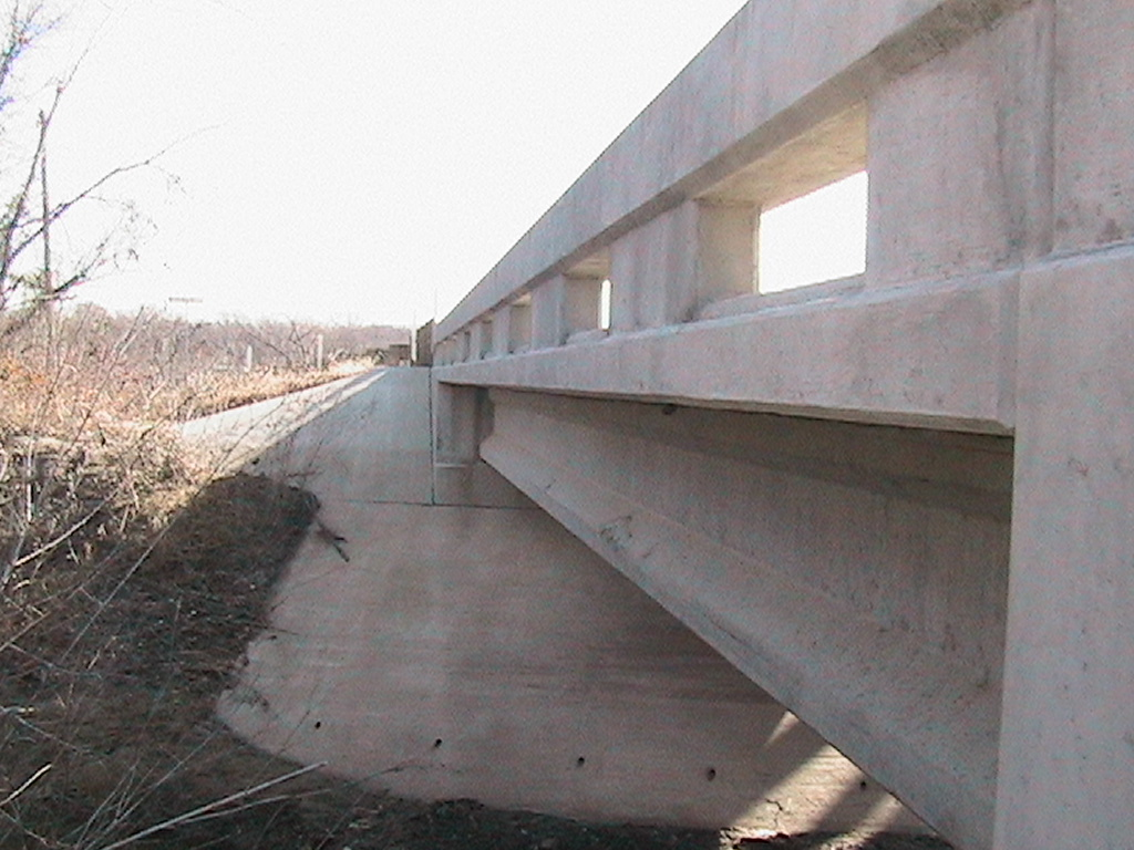 View of the concreate guard rail and the concreate slope to the ground below the bridge
