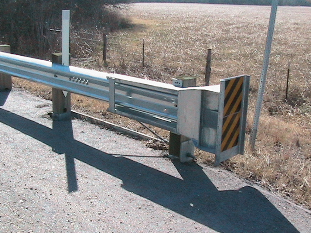 View of the beginning of a gaurd rail with the yellow and black stripped signal