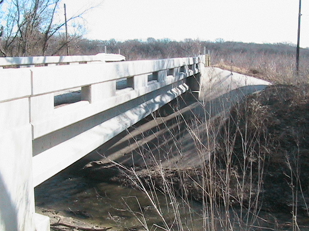 View of the side of the bridge with the rocks and grass below
