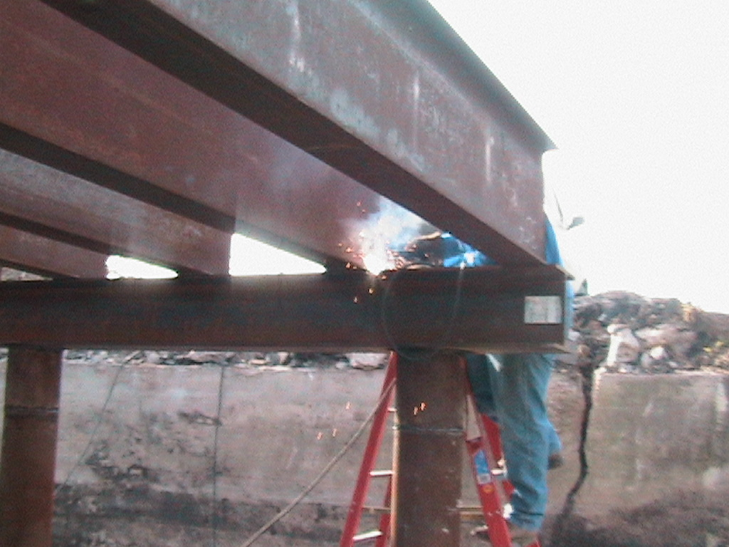 Man welding the beams together