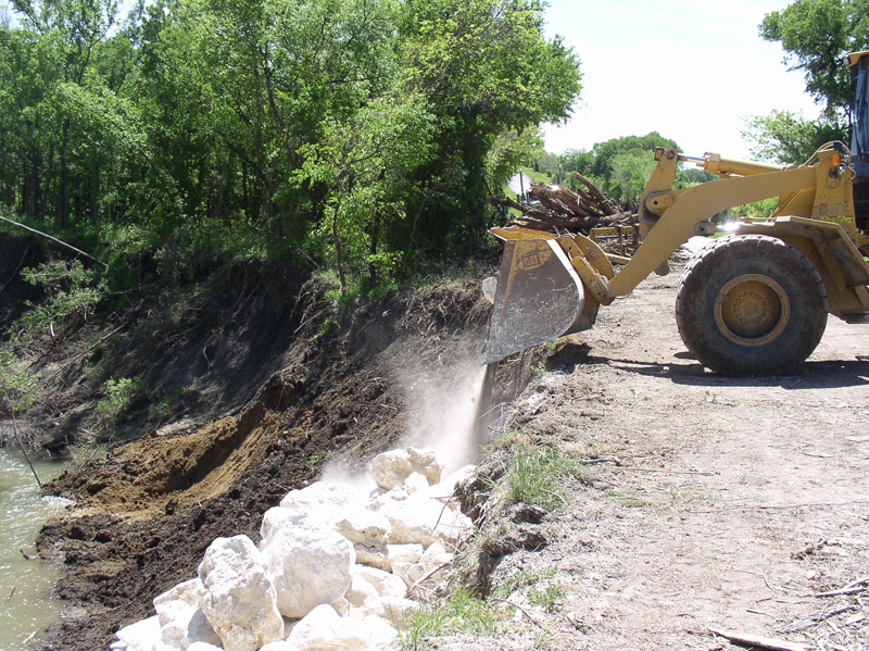 Tractor Equpiment pouring rocks down creek slope